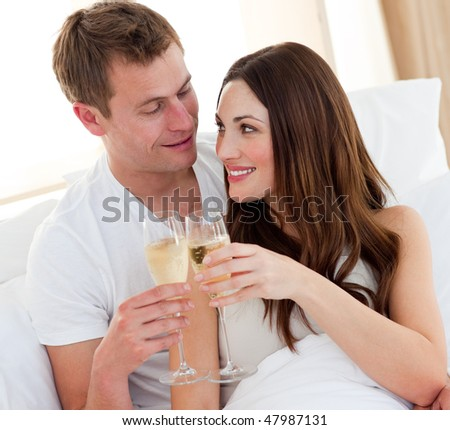 Romantic couple drinking champagne lying in bed at home