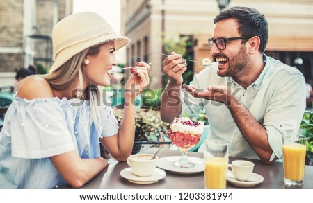 Romantic couple drinking coffee and enjoying in fruit desserts, having fun in the cafe. Dating, love, relationships
