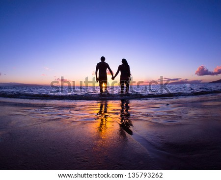 Romantic couple enjoying a beach walk at sunset