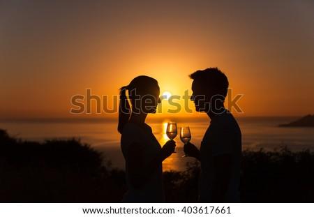 Romantic couple enjoying a glass of wine and beautiful sunset view.