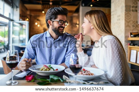 Romantic couple enjoying lunch in the restaurant, eating paste and drinking red wine. Lifestyle, love, relationships, food concept