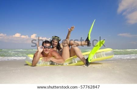 Romantic couple enjoying on an inflatable beach mattress