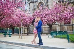 Romantic couple having a date in Paris on a spring day with beautiful cherry blossoms in the background. Tourists enjoying their vacation in France. Romantic date or traveling couple concept