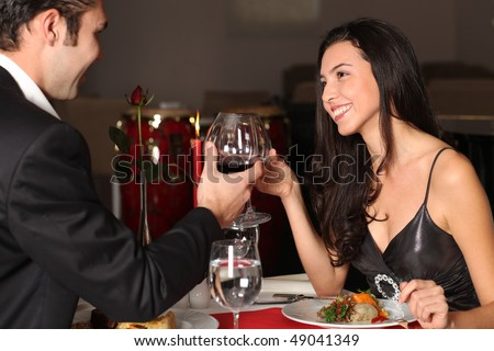Romantic couple having dinner, clinking glasses