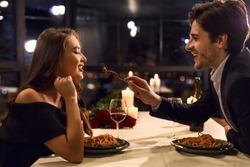 Romantic couple having dinner in restaurant, feeding each other. Eat my love concept
