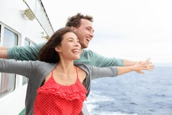 Romantic couple having fun laughing in funny pose on cruise ship boat. Smiling happy man and woman on travel vacation holidays on open ocean sea.