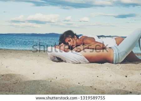 Romantic couple having fun on the beach. Happy couple running on beach at sunset. Sensual. Vacation. Sea background. Love game. Sensuality. Kiss.