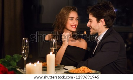Romantic couple having romantic dinner in restaurant, feeding each other. #1299691945