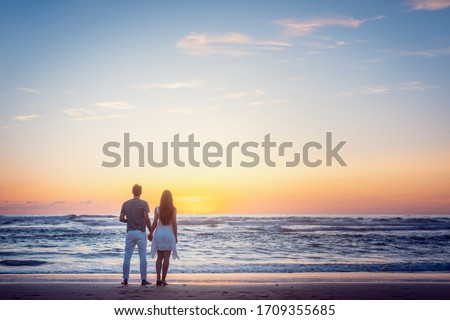 Photo of  Romantic couple holding hands in their vacation standing on a beach by the sea