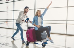 Romantic couple in airport. Attractive young woman and handsome man with suitcases are ready for traveling. Having fun on luggage trolley while waiting for departure.