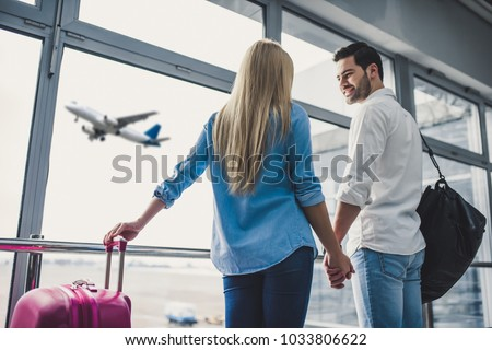 Romantic couple in airport. Attractive young woman and handsome man with suitcases are ready for traveling. Standing near panoramic windows while waiting for departure.