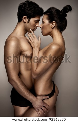 Romantic Couple In Lingerie standing sideways to camera with topless woman caressing mans cheek.