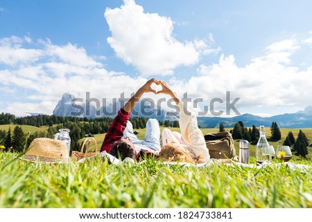 Romantic couple in love doing picnic visiting mountains alps. Boyfriend and girlfriend enjoying love doing heart shape with hands outdoor.