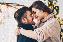 Romantic couple in love feeling happiness about their romance spending christmas eve together, woman and man enjoying perfect relationships and spending winter vacations in cozy home interior