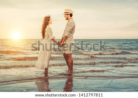 romantic couple in love holding hands in the beach
