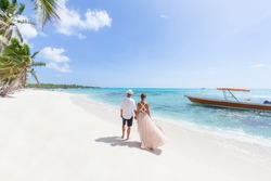 Romantic couple in love hugging, kissing and running on the sandy tropical Caribbean beach in Dominican republic landscape