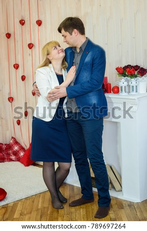 romantic couple in love in a room decorated with red hearts for Valentine's Day #789697264