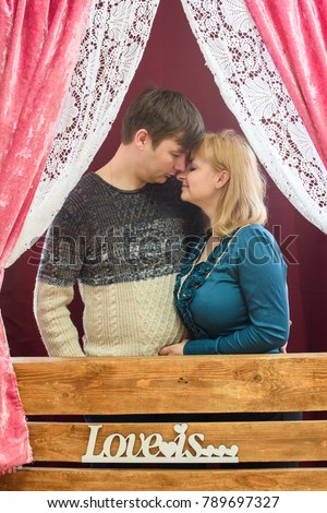 romantic couple in love in a room decorated with red hearts for Valentine's Day #789697327