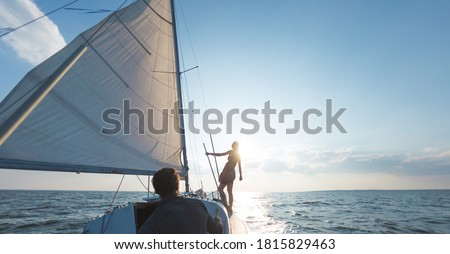 Romantic couple in love on sail boat at sunset under sunlight on yacht, A man and a woman are traveling on a sailing yacht.