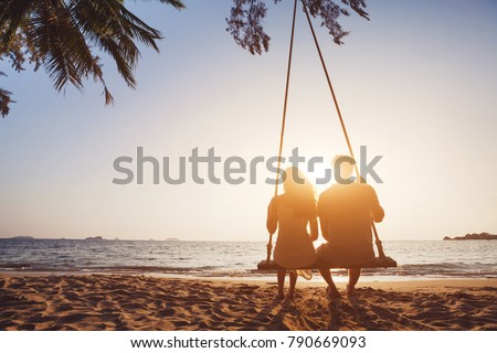 Photo of romantic couple in love sitting together on rope swing at sunset beach, silhouettes of young man and woman on holidays or honeymoon