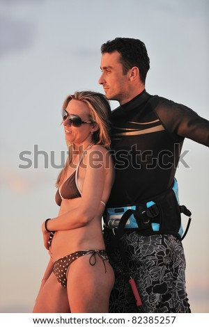 romantic couple in surf wear posing at beach on sunset at summer season
