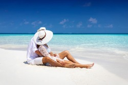 Romantic couple in white summer clothes sits hugging on a tropical beach in the Maldives and enjoys their honeymoon