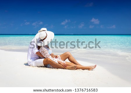 Romantic couple in white summer clothes sits hugging on a tropical beach in the Maldives and enjoys their honeymoon Stockfoto ©
