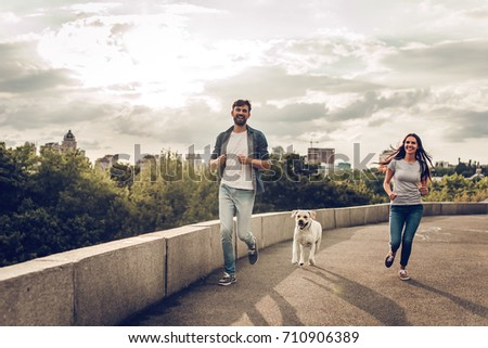 Romantic couple is on a walk in the city with their dog labrador. Beautiful young woman and handsome man are running and having fun outdoors with golden retriever labrador. #710906389