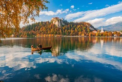 Romantic couple is sailing by boat on Bled lake. Castle rock with medieval fortress, colorful hills under beautiful sky reflected in lake water. Bled lake is best travel destination in Slovenia