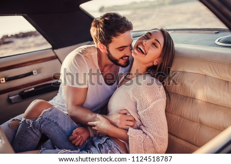 Romantic couple is sitting in green retro car on the beach. Handsome bearded man and attractive young woman in vintage classic car. Stylish love story. Hugging and kissing while being in car.