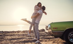 Romantic couple is standing near green retro car on the beach. Handsome bearded man and attractive young woman with vintage classic car. Love story.Muscle car
