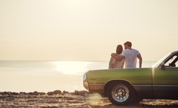 Romantic couple is standing near green retro car on the beach. Handsome bearded man and attractive young woman with vintage classic car. Love story.