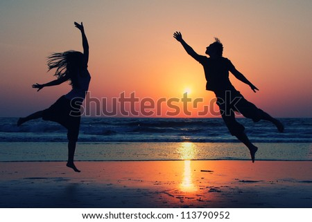 Romantic couple jumping on background of lake at sunset