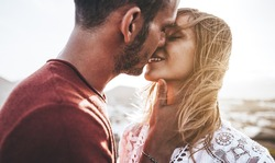 Romantic couple kissing at sunset - Boyfriend and girlfriend in love on a date outdoor