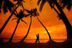 Romantic couple kissing at tropical beach with palm trees with sunset in the background