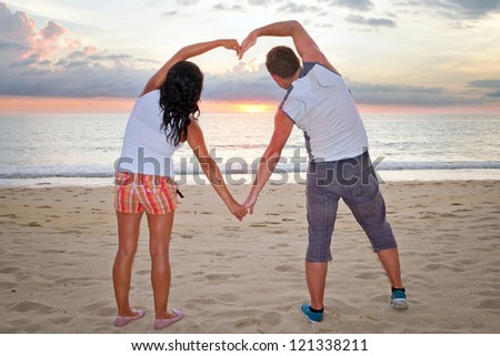 Romantic couple making heart shape with arms at sunset