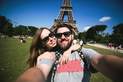 Romantic couple making selfie in front of Eiffel Tower while traveling in Paris, France. Happy smiling students enjoy their vacation in Europe.