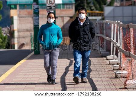 Romantic couple man and woman in respiratory masks during coronavirus pandemic in Cusco, Peru in Latin America. Epidemic of coronavirus covid-19