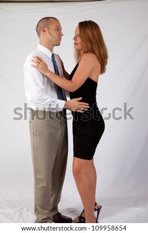 Romantic couple, man and woman, standing in an embrace and staring into each others eyes