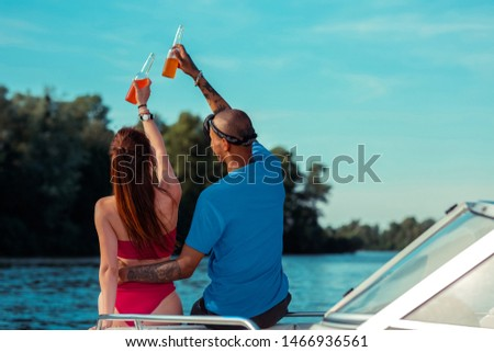 Romantic couple. Modern young people holding bottles of soft drinks while sitting on the deck of a pleasure boat