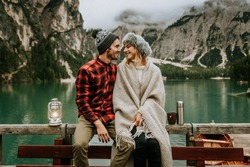 Romantic couple of adults visiting an alpine lake at Braies Italy. Tourist in love spending loving moments on a mountains background. Couple, wanderlust and travel concept.