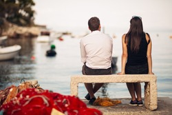 Romantic couple on a date in nature,sitting on the bench looking at serene ocean scene.People living on the coast lifestyle.Fishing town couple dating.Fisherman life.Navy sailors relationship