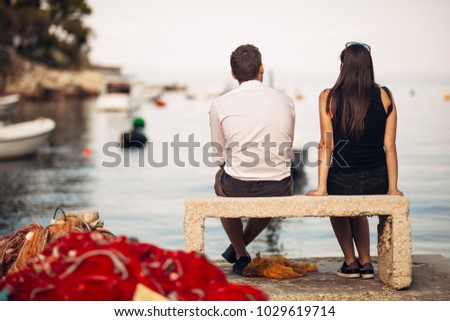 Romantic couple on a date in nature,sitting on the bench looking at serene ocean scene.People living on the coast lifestyle.Fishing town couple dating.Fisherman life.Navy sailors relationship #1029619714