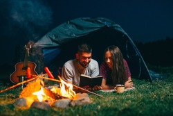romantic couple on night camping reading book . night scene with camping fire