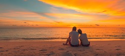 Romantic couple on the beach at colorful sunset on background. Beautiful tropical sunset scenery, romance couple sitting and watching the sunset sea and sky, horizon. Travel, honeymoon destination