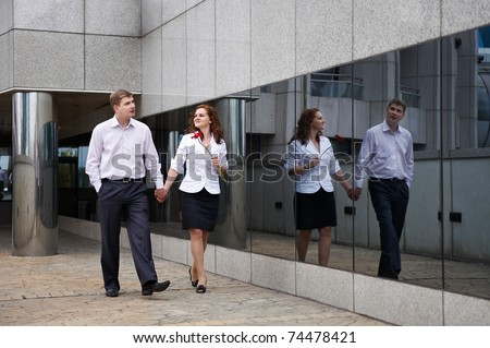 Romantic couple on walk along mirror of modern building in the city