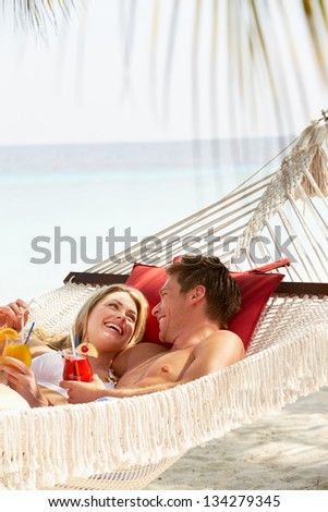 Romantic Couple Relaxing In Beach Hammock