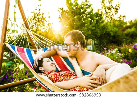 Romantic couple relaxing in flower garden hammock at sunset with rays. beautiful young couple relaxing in a hammock outdoor on the nature background  #582866953