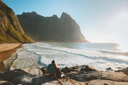 Romantic couple relaxing outdoor enjoying ocean view travel vacations lifestyle family man and woman together Kvalvika beach and rocks landscape in Norway