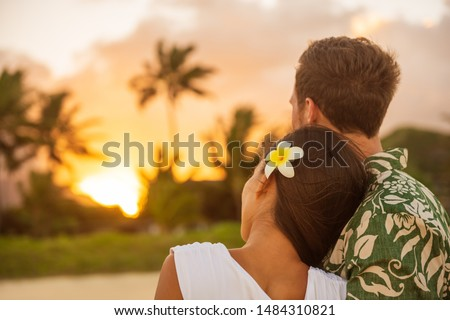 Romantic couple relaxing watching sunset on beach stroll view from back. Woman resting head on lover's shoulder on honeymoon vacation travel in summer Hawaii destination. Newlyweds people.
